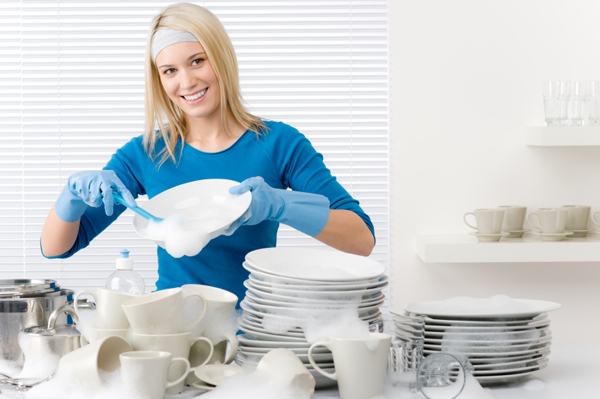 Washing dishes - happy woman in kitchen